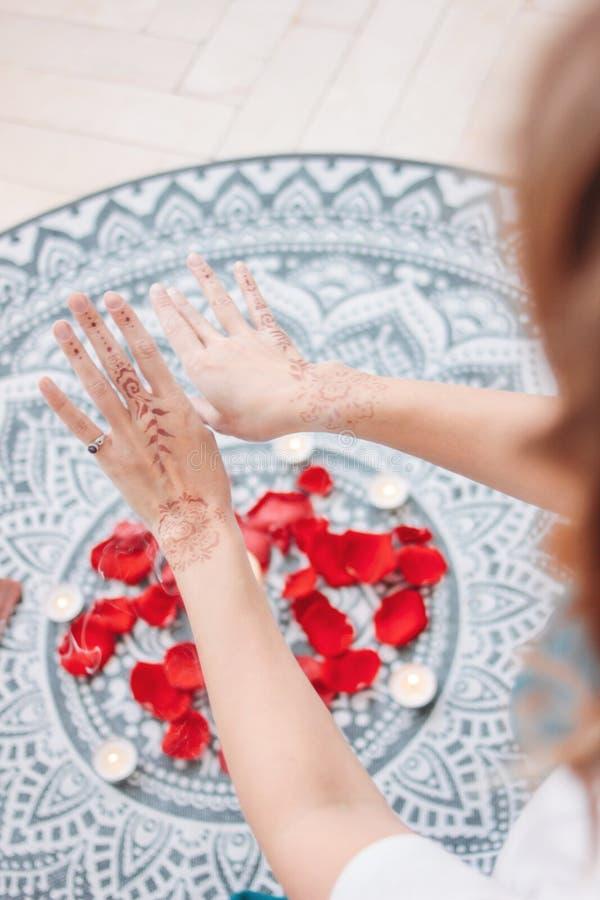 女性手舞蹈有mehendi的在蜡烛和玫瑰花瓣,妇女实践法坛  免版税库存照片
