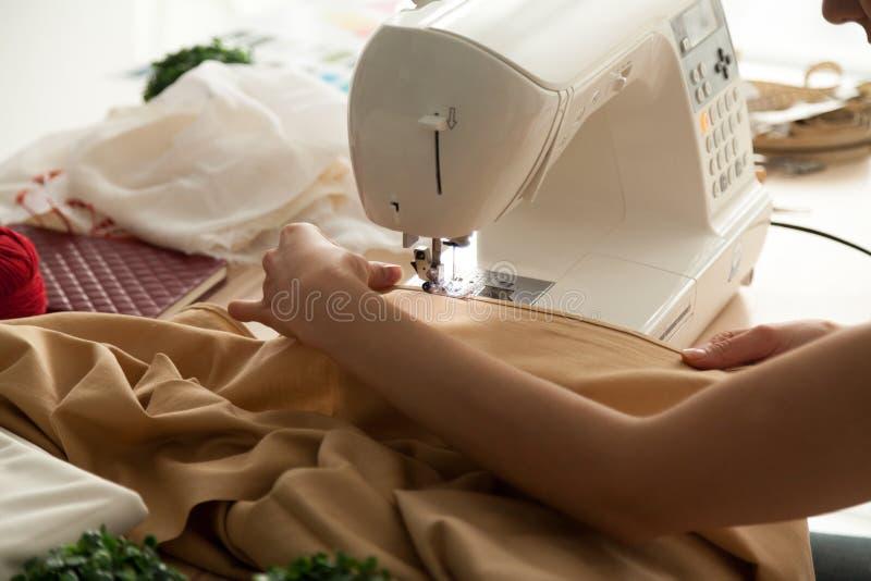 女性手藏品布料,运作在缝纫机关闭  图库摄影