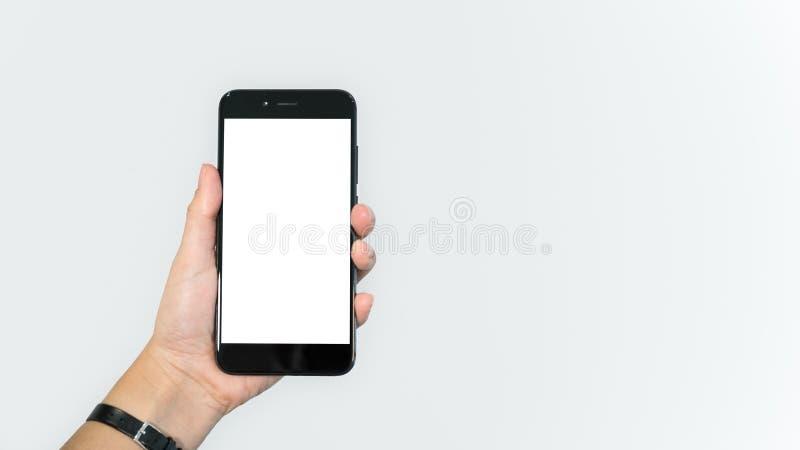 女性手藏品智能手机/流动手机,白色背景 免版税库存照片