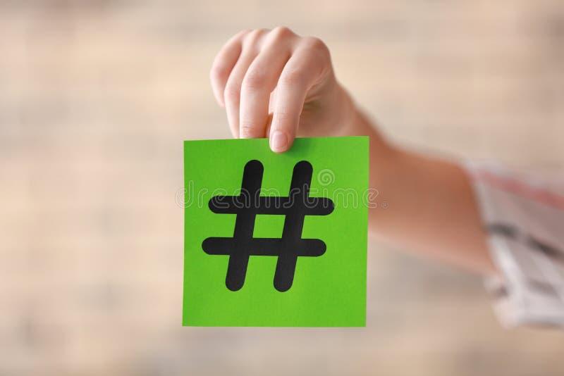 女性手藏品纸片与hashtag标志的在被弄脏的背景 库存图片