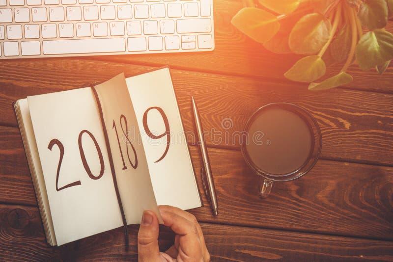 女性手轻碰笔记薄板料顶视图在木桌上的 2018年转动, 2019年是打开,被定调子 免版税图库摄影