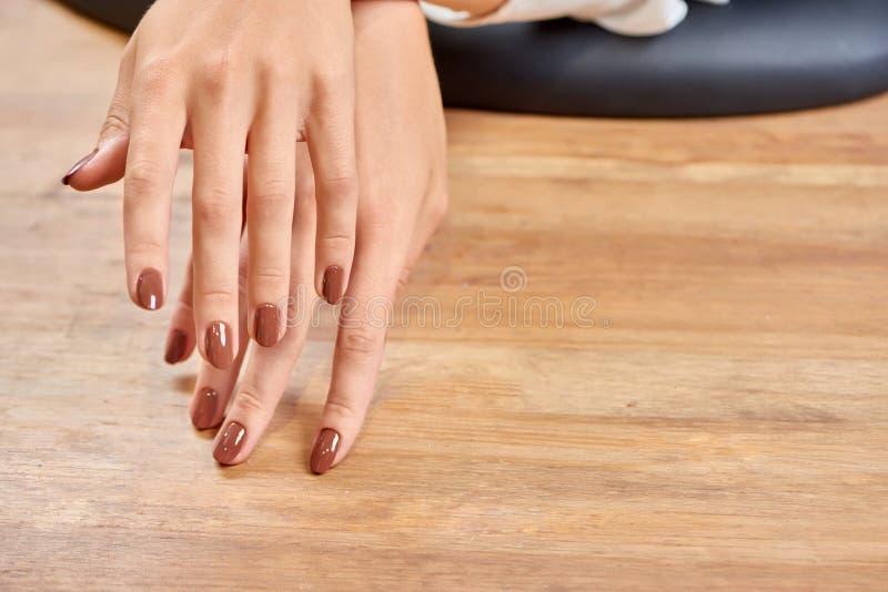 女性手选择聚焦有美妙的棕色修指甲的 库存图片