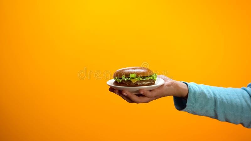 女性手陈列乳酪汉堡,便当餐馆的邀请的顾客 免版税库存照片