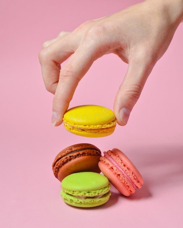 女性手降低黄色蛋白杏仁饼干曲奇饼 在桃红色淡色背景的许多蛋白杏仁饼干 简单派 免版税库存照片