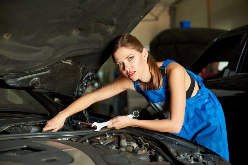 女性技工修理有板钳的汽车 库存照片