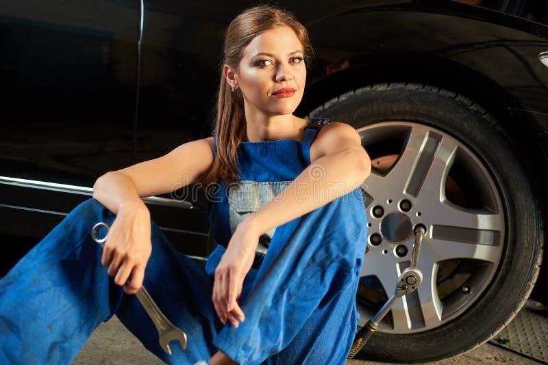 女性技工在拿着板钳的轮胎附近坐 免版税库存照片