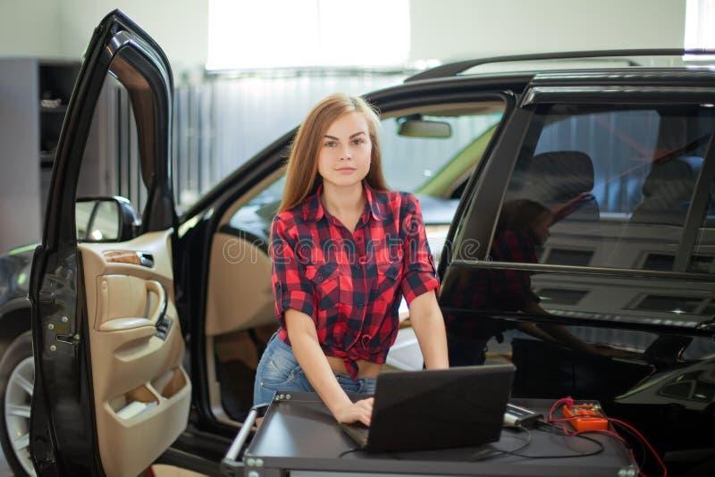 女性技工在控制中衬衣在工作 自动服务站 免版税库存图片
