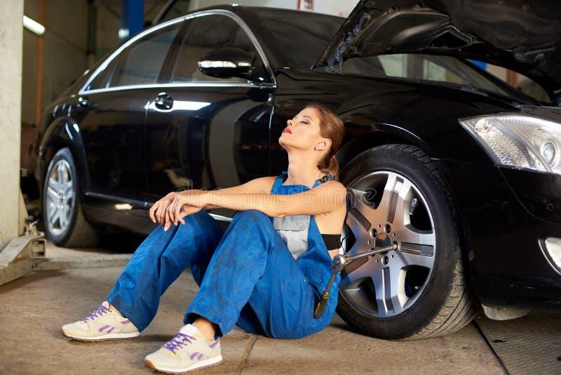 女性技工在汽车附近享受她的断裂在修理它以后 库存照片