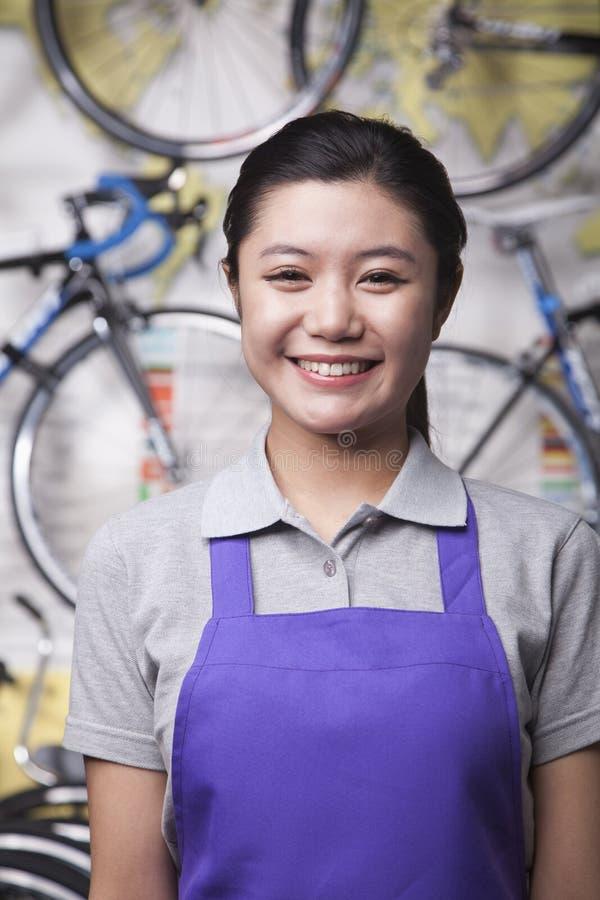 年轻女性技工画象在自行车商店,北京 库存图片