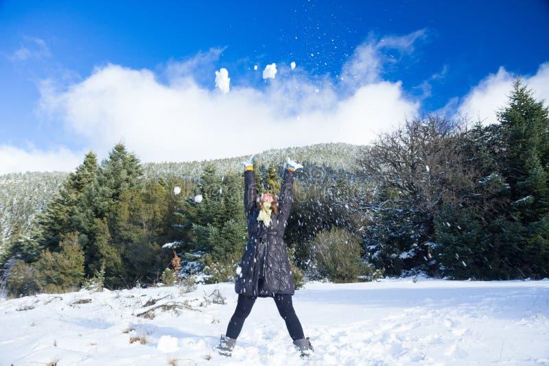 女性投掷的雪剥落的行动片刻在天空中在与冷杉木的一座多雪的山在背景中在白天 免版税库存照片