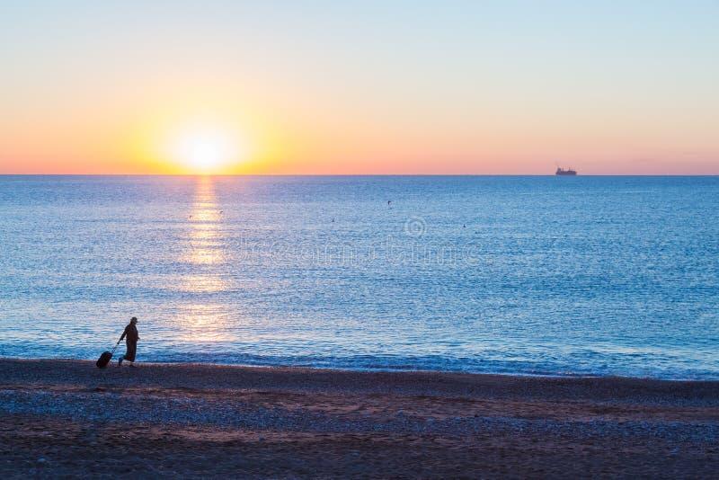 女性拉扯的旅行手提箱异乎寻常的假期剪影沿海洋海滩的 图库摄影