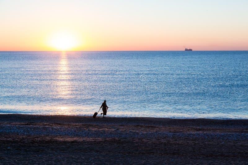 女性拉扯的旅行手提箱异乎寻常的假期剪影沿海洋海滩的 免版税图库摄影