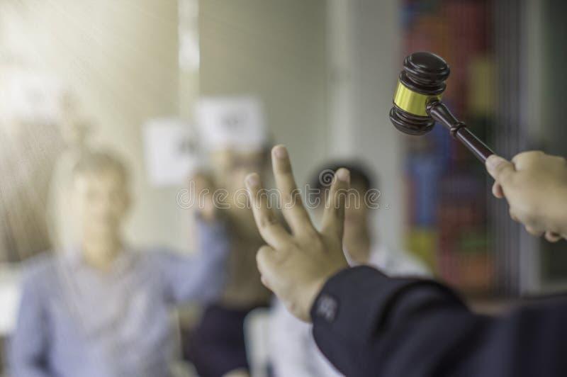 女性拍卖控制举行第3只手和指向锤子出价优胜者 免版税库存图片