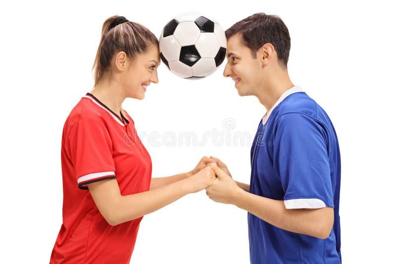 女性拿着橄榄球betwe的足球运动员和一个男性足球运动员 库存图片