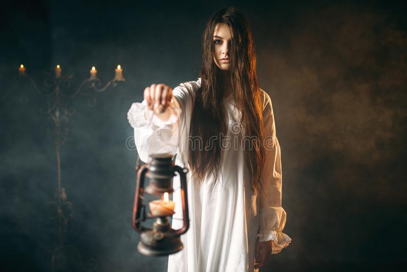 女性拿着煤油灯,黑暗的魔术 库存照片