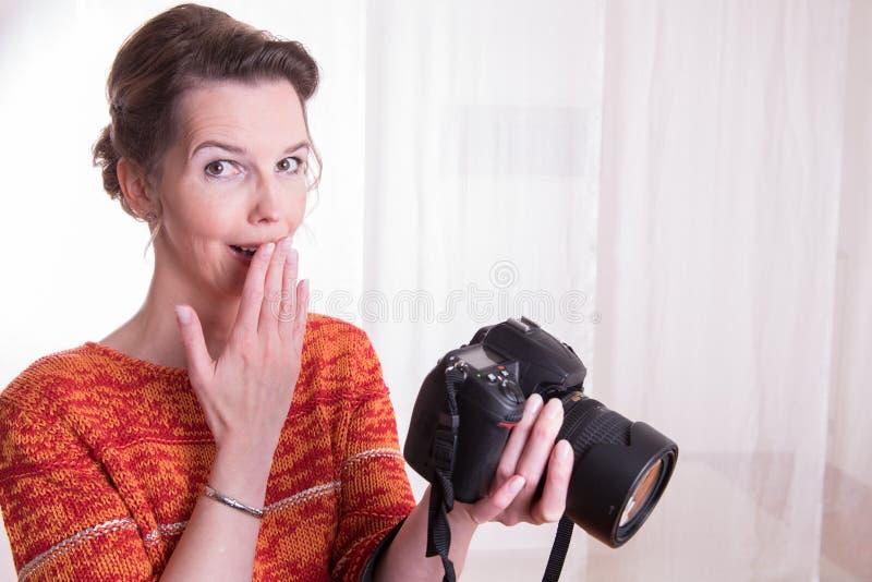 女性摄影师在与照相机一起使用 免版税库存图片