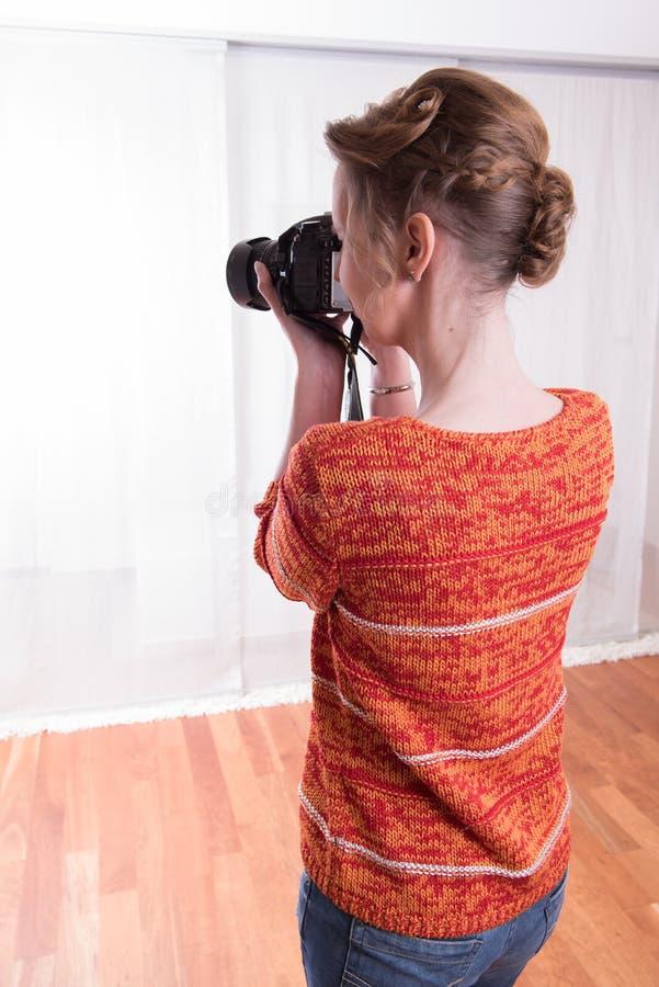 女性摄影师在与照相机一起使用 免版税库存照片