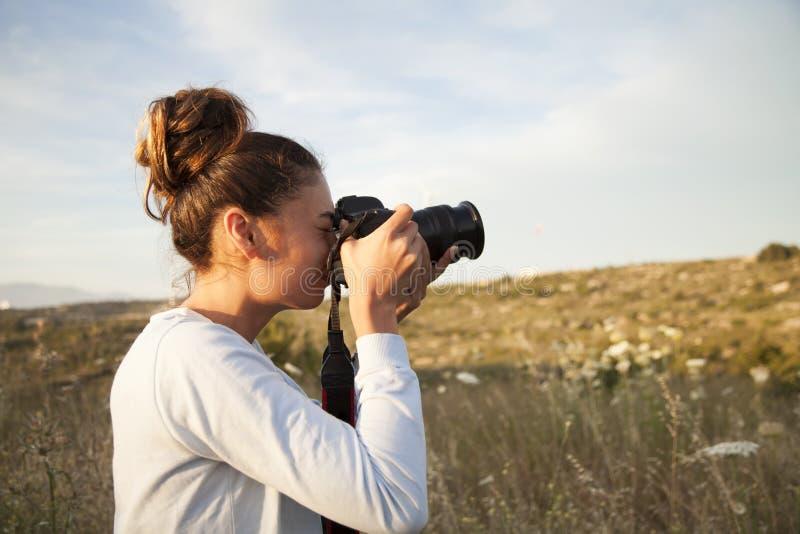女性摄影师,为山风景照相在日落在户外 库存照片