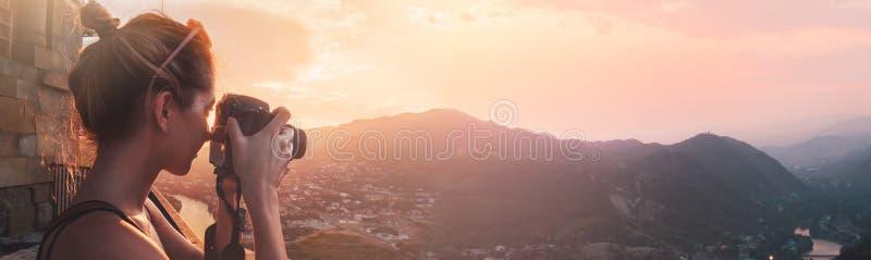 女性摄影师,为山风景照相在日落,长期全景 库存图片
