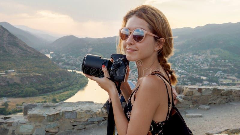 女性摄影师,为山风景照相在日落 免版税库存图片
