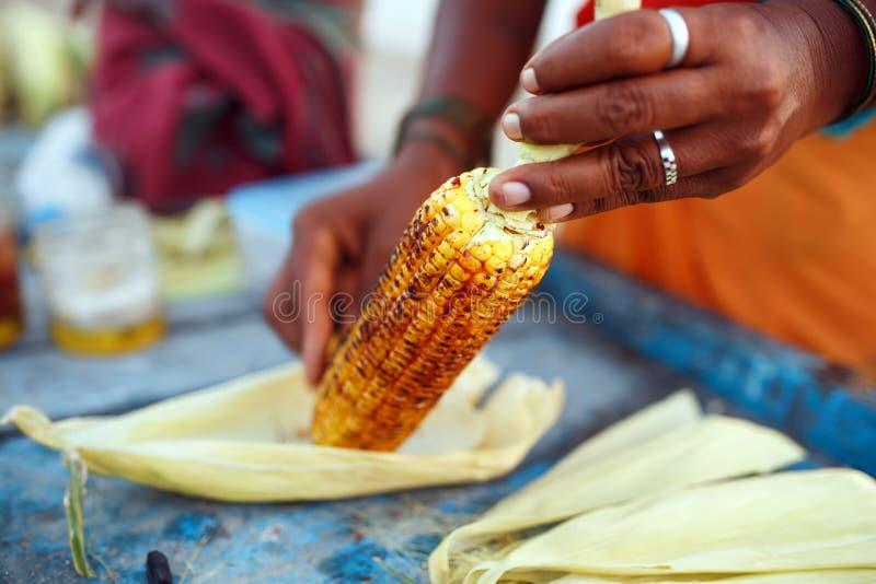 女性摊贩的特写镜头手用柠檬和香料摩擦一个烤甜玉米玉米棒 印度街道食物概念, 库存照片