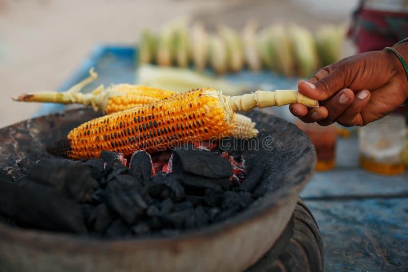 女性摊贩的特写镜头手用柠檬和香料摩擦一个烤甜玉米玉米棒 印度街道食物概念, 免版税库存图片