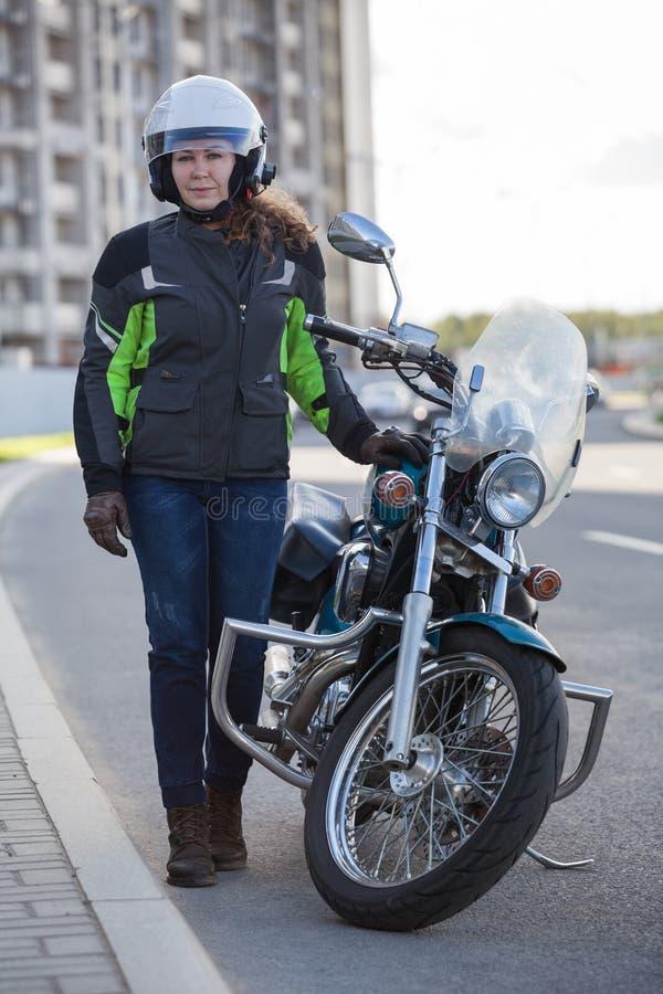 女性摩托车骑士全长画象站立在都市路的经典自行车附近的安全成套装备的 图库摄影