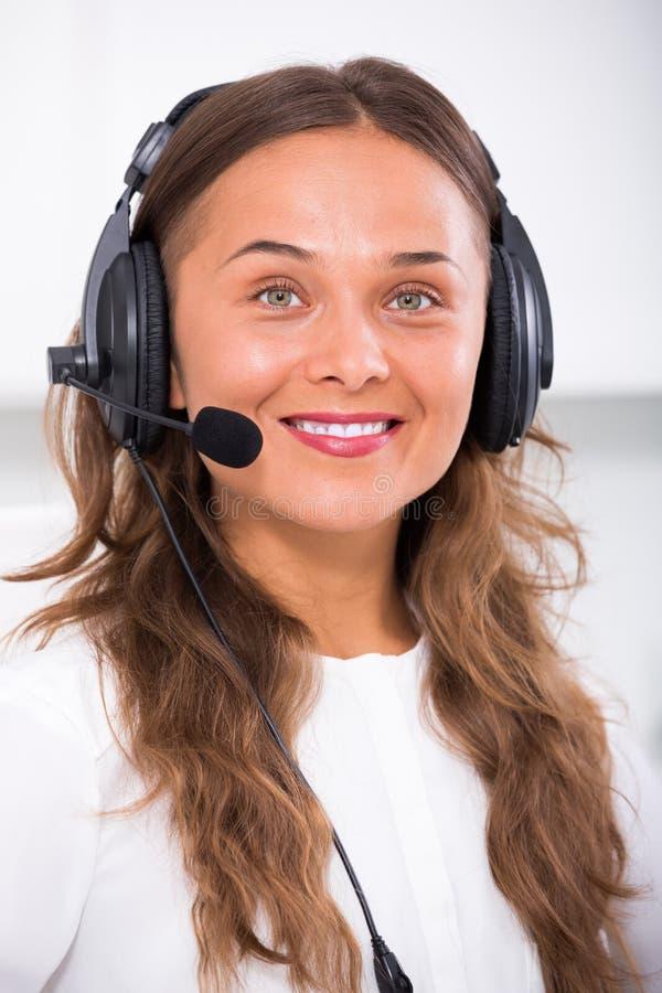 女性操作员谈话与使用耳机的顾客 图库摄影