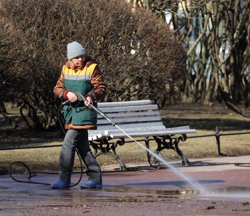 女性擦净剂在公园做湿清洗的道路 图库摄影
