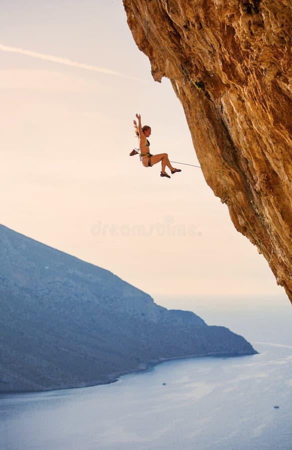 女性攀岩运动员落峭壁,当带领上升时 库存照片