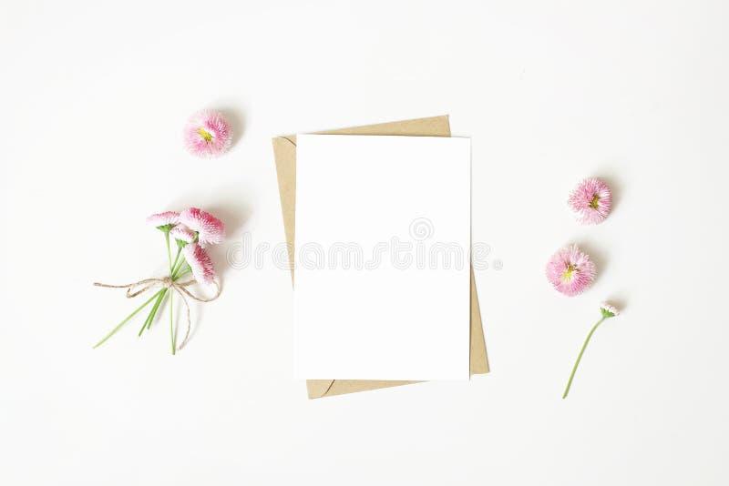 女性文具,桌面大模型场面 垂直的空白的贺卡、工艺纸信封和雏菊花束和 免版税库存照片