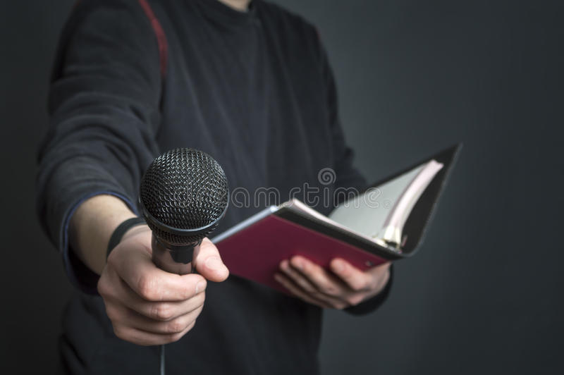 女性新闻工作者在拿着话筒和笔记的新闻招待会 图库摄影