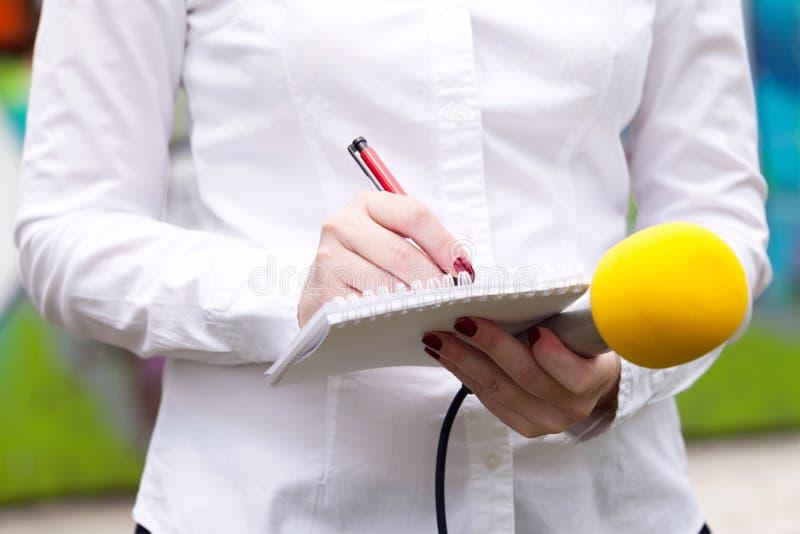 女性新闻工作者在新闻发布会,写笔记,拿着话筒 免版税库存照片