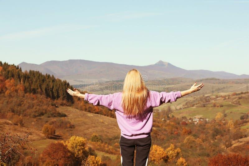 女性旅客感觉自由在山 免版税图库摄影