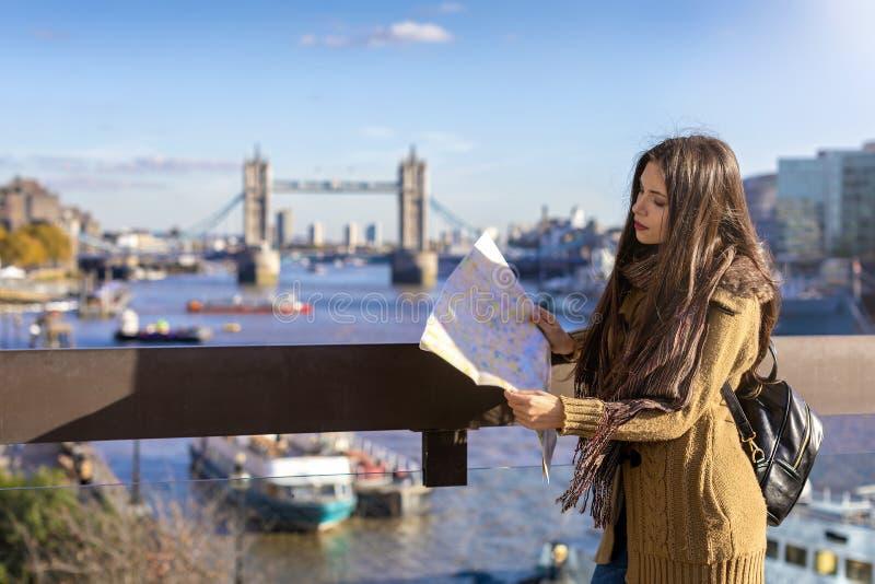 女性旅客看在伦敦塔桥前面的街道地图在伦敦,英国 免版税库存图片