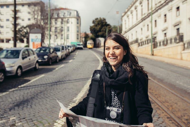 女性旅客藏品和读书游人地图 免版税库存照片