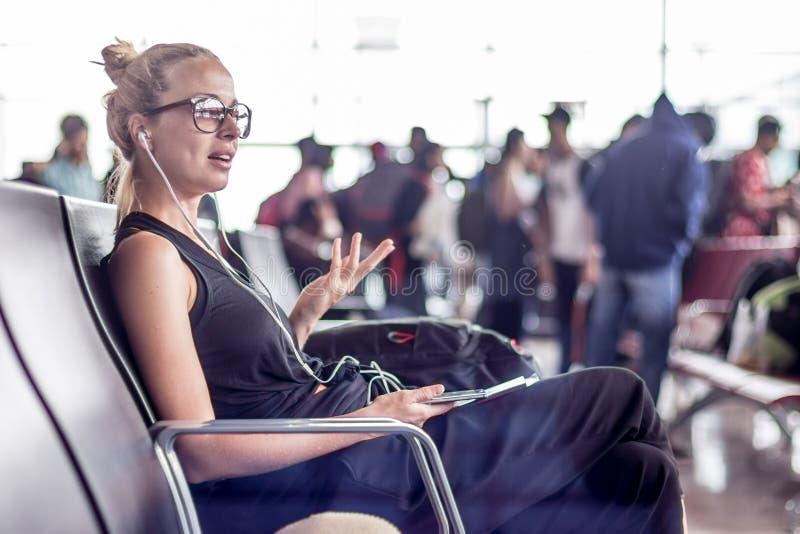 女性旅客谈话在手机,当等待上飞机在登机口在亚洲机场终端时 免版税库存图片