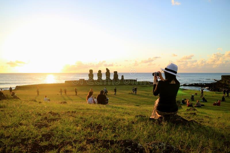女性旅游为著名日落场面照相在Ahu Tahai,复活节岛的,智利考古学站点 免版税图库摄影