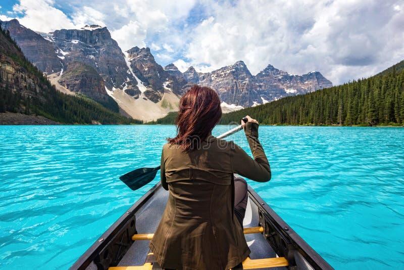 女性旅游乘独木舟在梦莲湖在班夫国家公园,加拿大人罗基斯,阿尔伯塔,加拿大 免版税库存照片