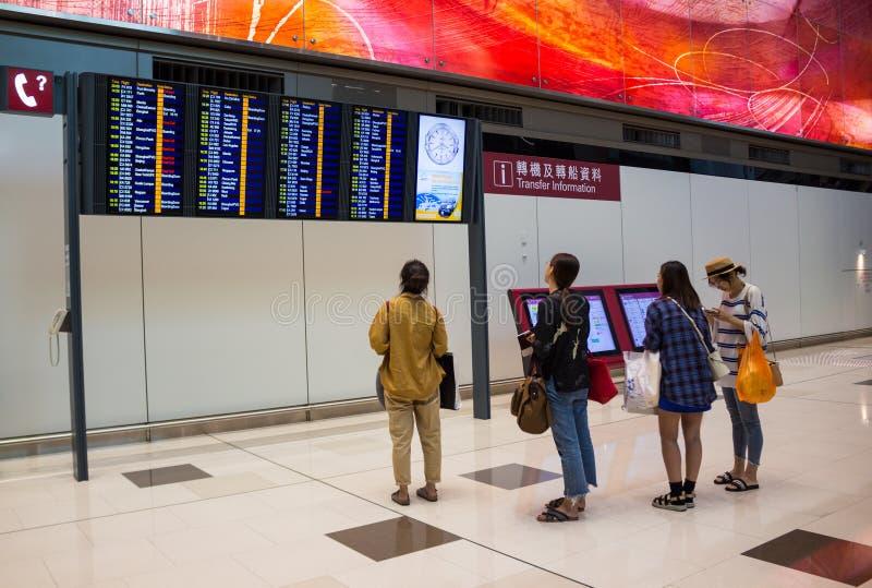 女性旅行家检查离开在机场终端上 免版税库存照片