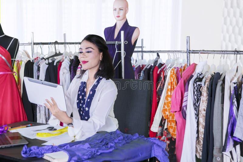 女性时尚编辑与片剂一起使用 免版税库存图片