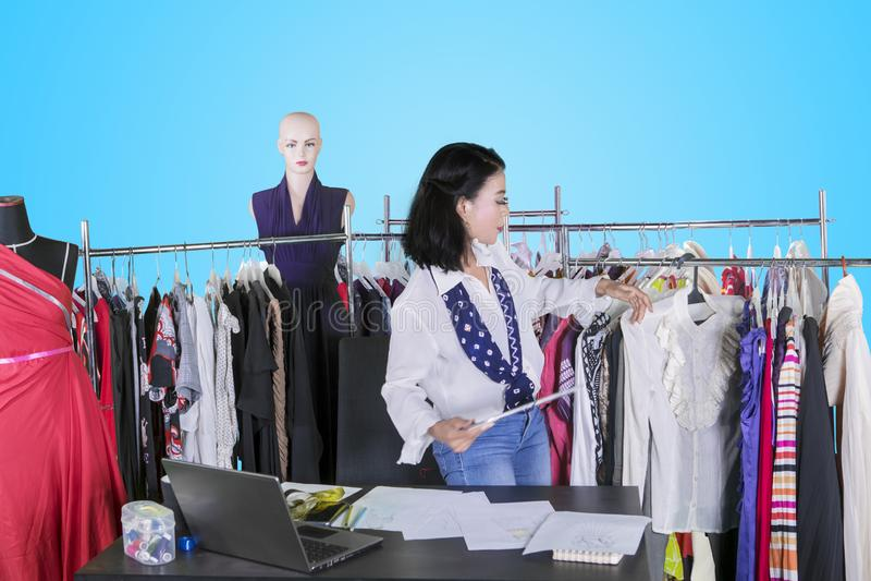 女性时尚编辑在机架附近拿着一种片剂 库存照片