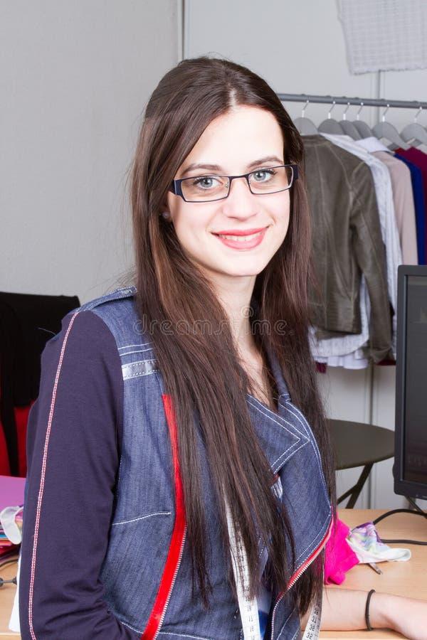 女性时装设计师在她的车间时髦的陈列室里工作 库存照片