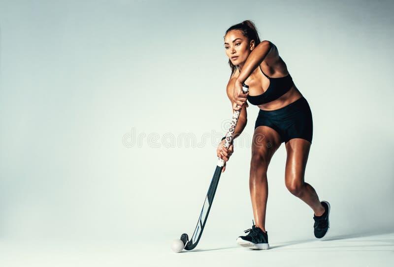 女性曲棍球运动员滴下的球 免版税库存图片