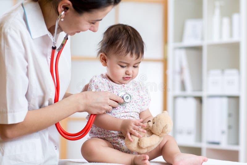 女性有听诊器的医生审查的儿童小孩 免版税库存图片