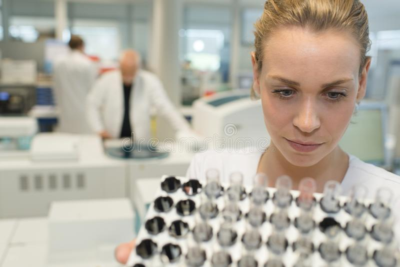 女性有长的吸移管的实验室化学家充分的试管 免版税库存图片