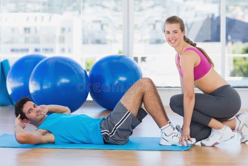 女性有他的锻炼的教练员帮助的人在健身房 免版税图库摄影