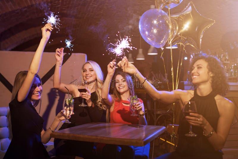 女性朋友享受生日聚会获得与烟花闪烁发光物的乐趣喝酒精鸡尾酒坐的小组 图库摄影