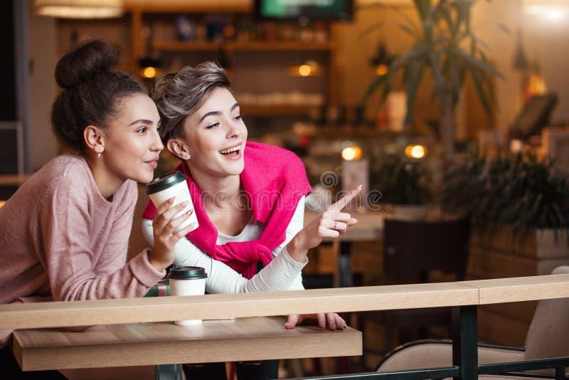 女性朋友吃午餐在笑和微笑在购物以后的购物中心咖啡馆 图库摄影