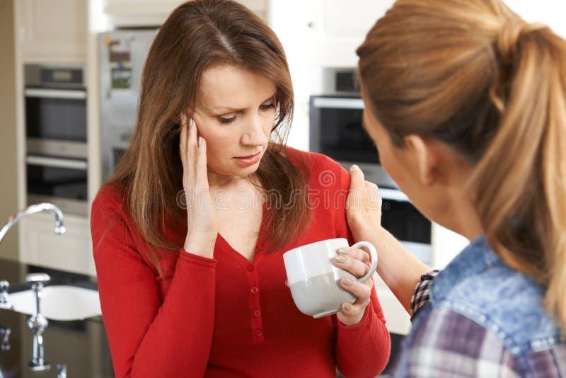 女性朋友在家被慰问的哀伤的妇女 免版税库存照片